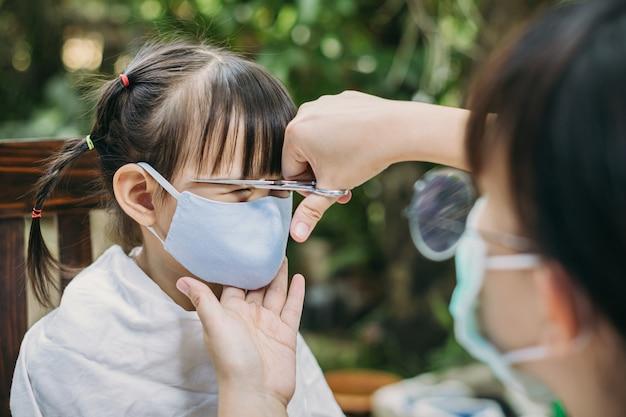 Dziecko noszące maskę na twarz w celu zapobiegania koronawirusowi podczas strzyżenia włosów w salonie fryzjerskim