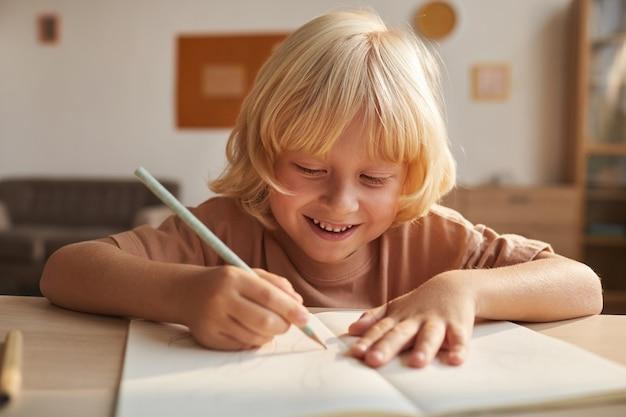 Dziecko o blond włosach pisząc raport w notesie odrabia lekcje po szkole