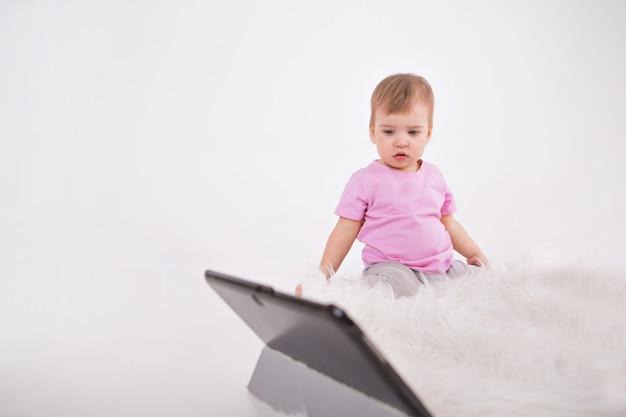 Dziecko ogląda bajki na tablecie. szkolenie domowe dla dziewczynki podczas kwarantanny