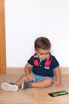 Dziecko ogląda filmy na telefon komórkowy z czerwonymi słuchawkami i granatową koszulą
