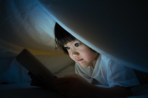 Dziecko oglądając tablet na łóżku w nocy