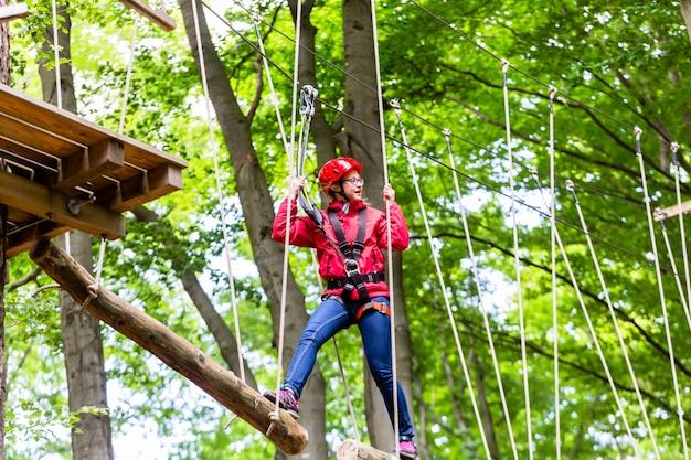 Dziecko osiągające platformę wspinaczkową w wysokim parku linowym