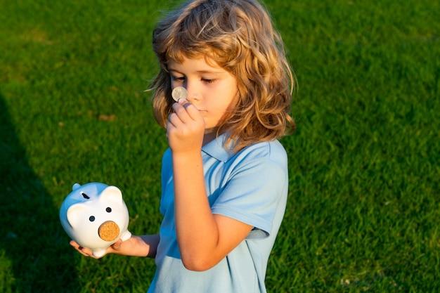 Dziecko oszczędności monety z skarbonka. gotówka i inwestycje. chłopiec zbierający pieniądze do skarbonki skarbonki. dziecko wkłada pieniądze do skarbonki. dziecko z skarbonką.