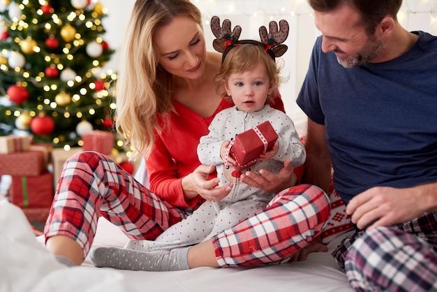 Dziecko otwierające świąteczny prezent z rodzicami w łóżku