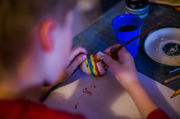 Dziecko ozdabia pisankę w kolorach tęczy. dziecko trzyma jajko i maluje je pędzelkiem. przygotowanie do obchodów wielkanocy.