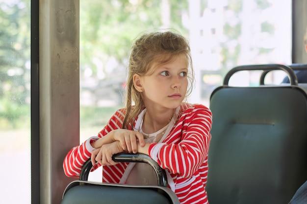 Dziecko pasażera autobusu miejskiego, trolejbusu, kobieta siedząca na siedzeniu pasażera