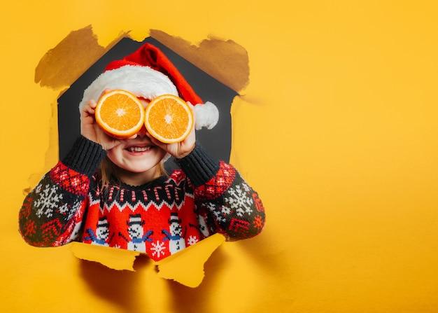 Dziecko patrzące na świąteczny prezent przez pomarańczę na czarnym tle