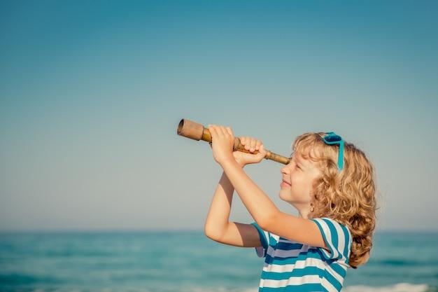 Dziecko patrzące przez lunetę na tle morza i nieba