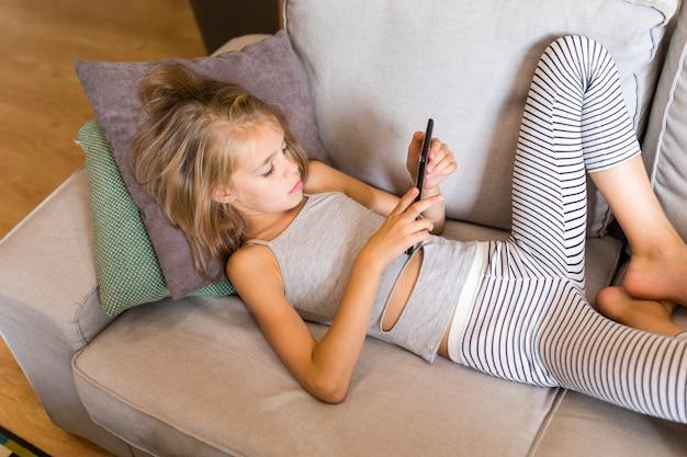 Dziecko patrzeje jej telefon i siedzi na kanapie