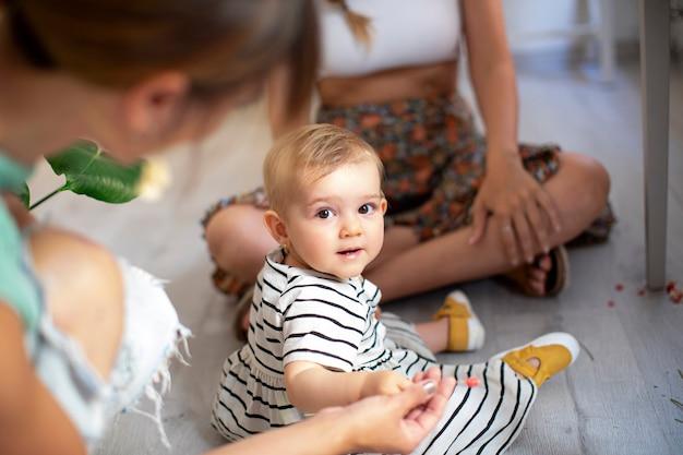 Dziecko patrzeje kamerę i siedzi na podłoga z dwie kobietami