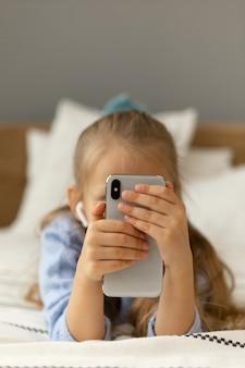 Dziecko patrzy na ekran telefonu. dziecko korzysta z telefonu.