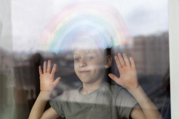 Dziecko patrzy przez okno z malowaną tęczą