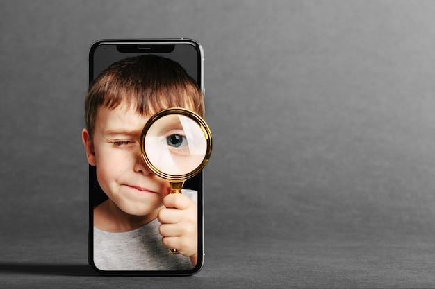 Dziecko patrzy w lupę przez telefon