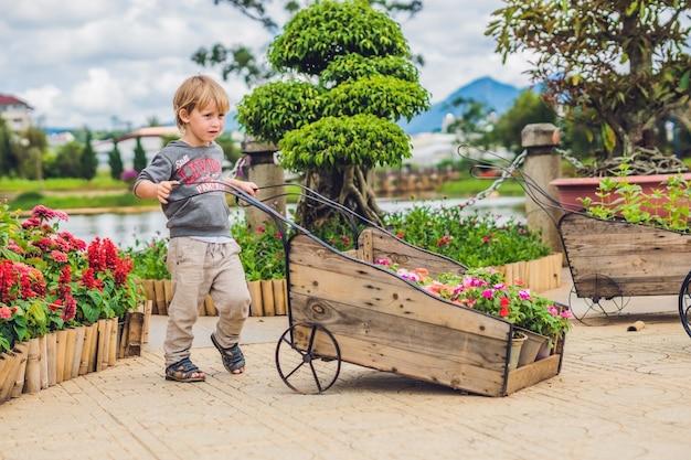 Dziecko pchające wózek na kółkach w ogrodzie