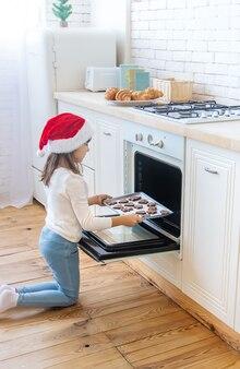 Dziecko piecze i smakuje świąteczne ciasteczka