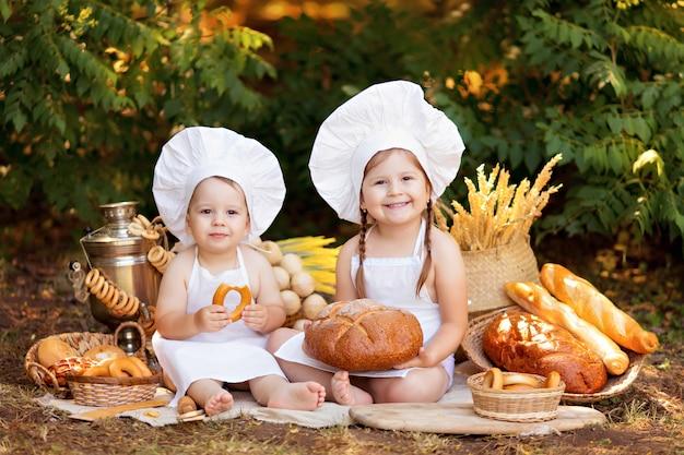 Dziecko piekarz na pikniku je chleb i bułeczki w białym fartuchu