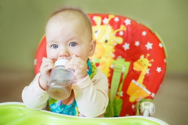 Dziecko pijące z butelki siedzącej w krzesełku do karmienia