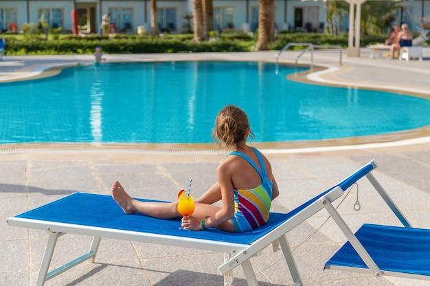 Dziecko pije koktajl przy basenie