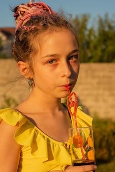 Dziecko pije sok w barze przy basenie. letnie rodzinne wakacje z dziećmi. mała dziewczynka trzyma świeży koktajl ananasowy