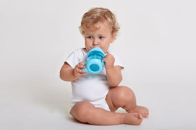 Dziecko pije z kubka dziecka, siedząc na podłodze i odwracając wzrok, ubrany w kombinezon