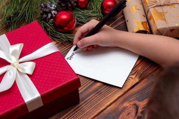 Dziecko piszące list do świętego mikołaja na drewnianym stole ze świątecznymi i noworocznymi dekoracjami