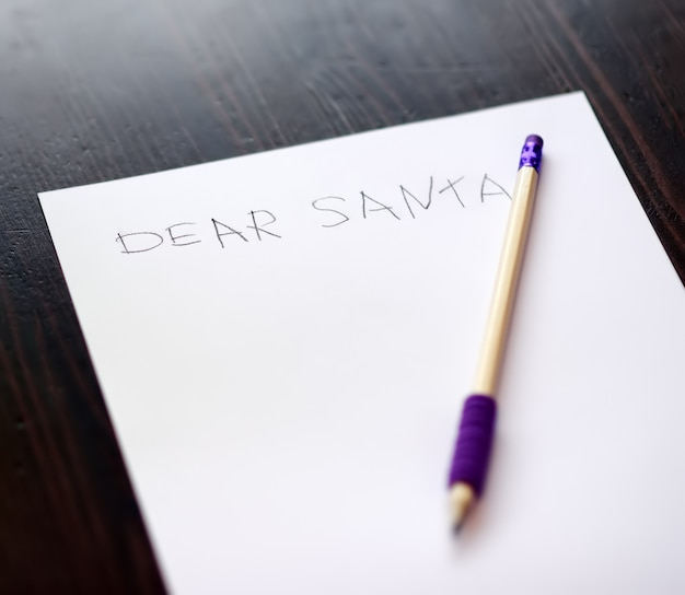 Dziecko pisze list do świętego mikołaja. dzieciak marzy o darze, który może otrzymać.