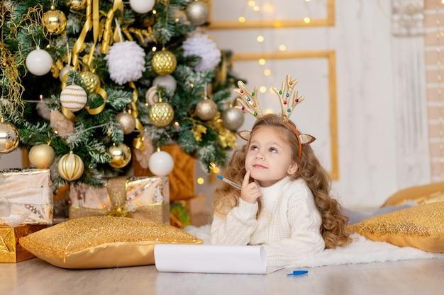 Dziecko pisze list do świętego mikołaja pod choinką ze złotym dekorem