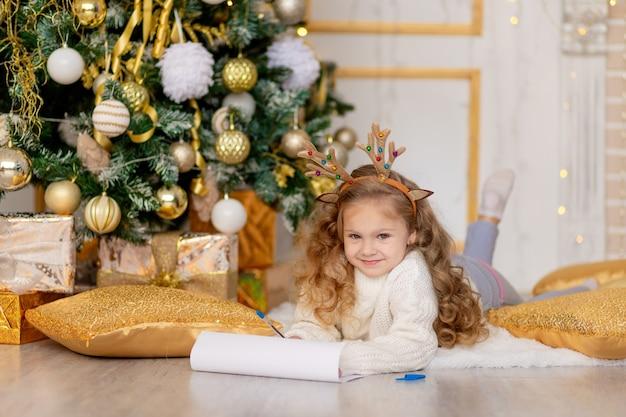 Dziecko pisze list do świętego mikołaja pod ozdobioną złotem choinką