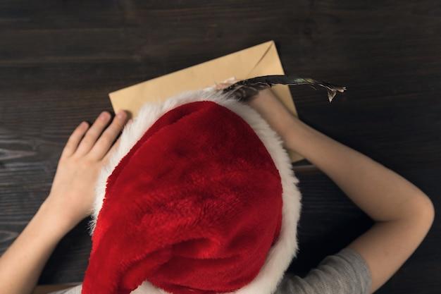 Dziecko pisze list do świętego mikołaja w czapce świętego mikołaja. widok z góry. boże narodzenie