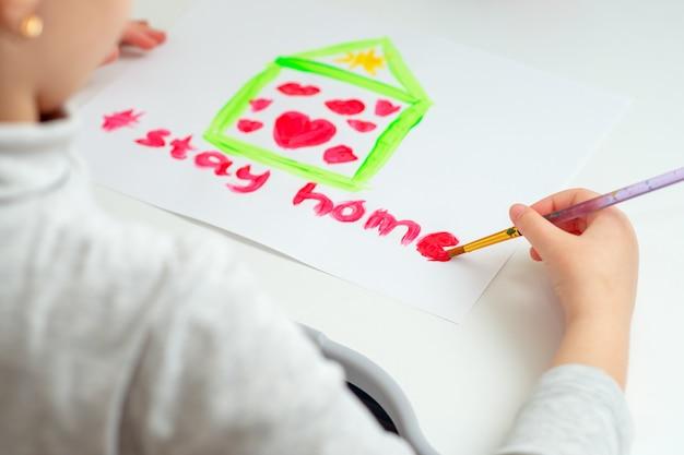 Dziecko pisze słowa zostań w domu