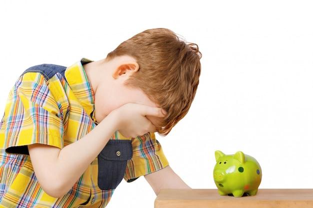 Dziecko płacze blisko prosiątko banka.