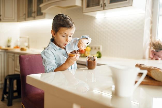 Dziecko płci męskiej rozmazuje rozpuszczoną czekoladę na chlebie.