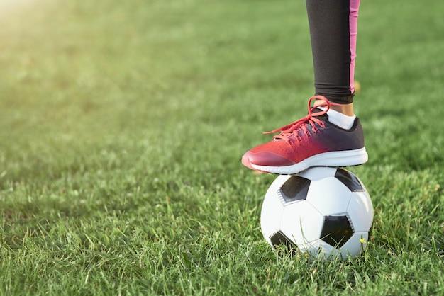 Dziecko płci żeńskiej z piłką nożną stojącą na trawie