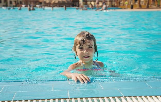 Dziecko pływa i nurkuje w basenie. selektywne skupienie.