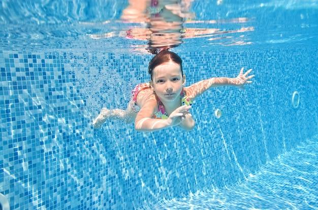 Dziecko pływa pod wodą w basenie mała dziewczynka nurkuje i bawi się pod wodą