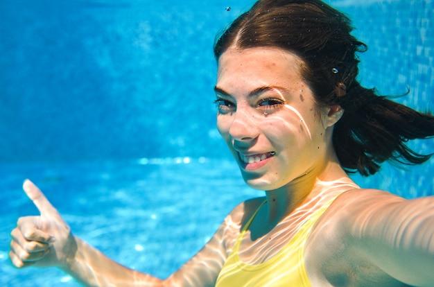 Dziecko pływa pod wodą w basenie, szczęśliwa aktywna nastolatka nurkuje i bawi się pod wodą, fitness dla dzieci i sport na rodzinne wakacje w kurorcie