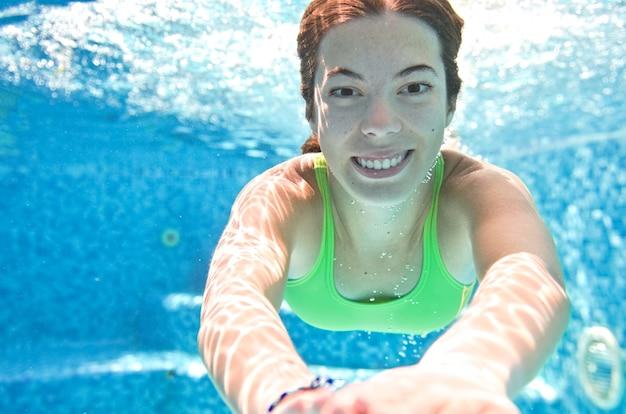 Dziecko pływa pod wodą w basenie szczęśliwa aktywna nastolatka nurkuje i bawi się pod wodą