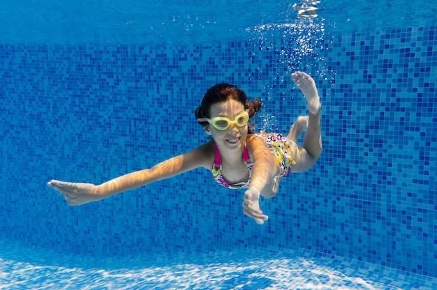 Dziecko pływa w basenie pod wodą, szczęśliwa aktywna dziewczyna nurkuje i bawi się pod wodą, fitness dla dzieci i sport podczas rodzinnych wakacji w kurorcie