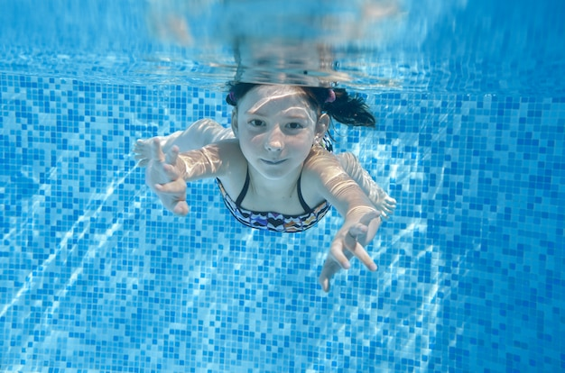 Dziecko pływa w basenie pod wodą, szczęśliwa aktywna dziewczyna nurkuje i bawi się w wodzie, fitness dla dzieci i sport na rodzinne wakacje