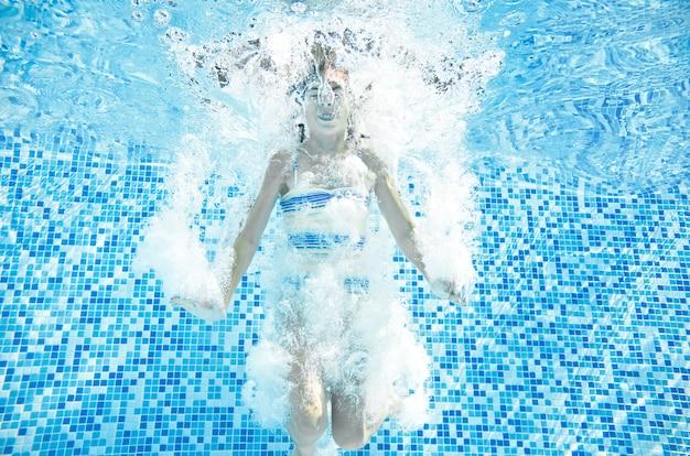 Dziecko pływa w basenie pod wodą szczęśliwa aktywna dziewczyna skacze nurkując i bawi się pod wodą