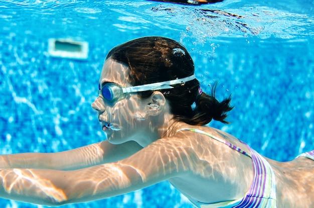 Dziecko pływa w basenie pod wodą, szczęśliwa aktywna dziewczyna w goglach dobrze się bawi w wodzie, sport dla dzieci na wakacjach rodzinnych