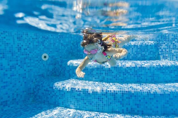 Dziecko pływa w basenie pod wodą