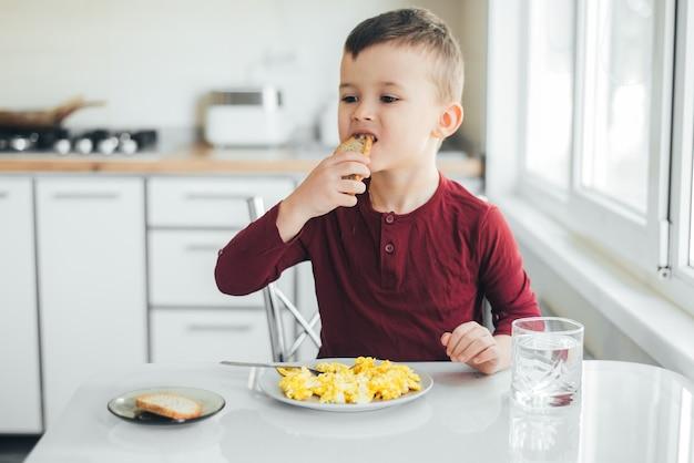 Dziecko po południu w białej kuchni w bordowym swetrze zjada omlet