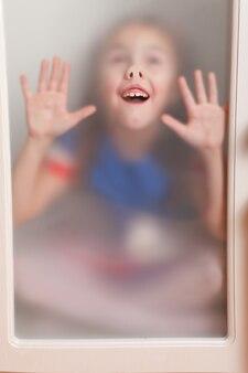 Dziecko pochylony twarz do szkła i robi śmieszną minę.