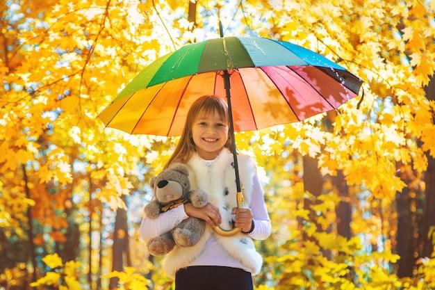Dziecko pod parasolem w jesień parku. selektywne ustawianie ostrości.