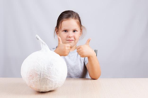 Dziecko pokazuje kciuki do góry i trzyma domowej roboty dynię zrobioną z serwetek i papieru, co jest hobby dla samoizolacji