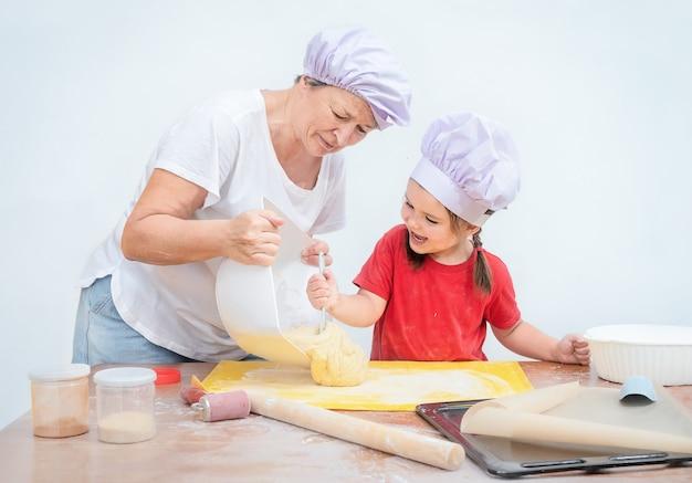 Dziecko pomaga babci wypiekać piekarnię. kobieta uczy wnuczkę gotować