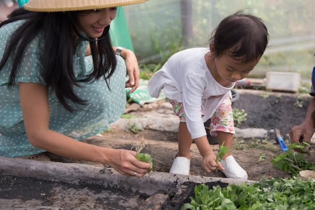 Dziecko pomaga matce sadzącej nasiona w gospodarstwie