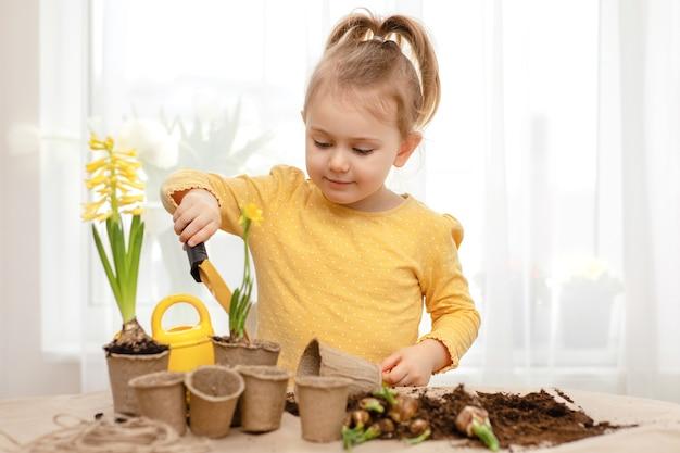 Dziecko pomagające w pielęgnacji kwiatów i roślin w pomieszczeniach używa żółtych narzędzi ogrodniczych