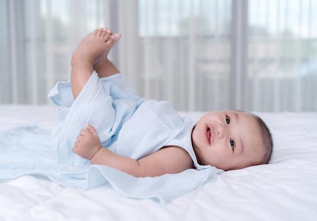 Dziecko porusza nogą w powietrzu na łóżku